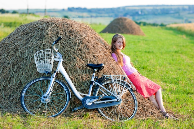 Young woman with a bicycle on field with haystacks