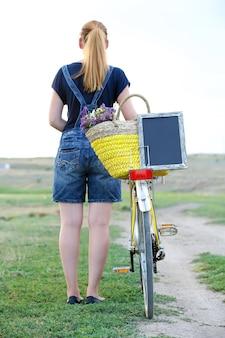 일몰시 풀밭에서 자전거와 함께 젊은 여성