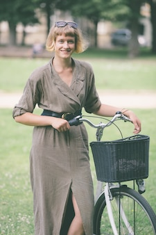Young woman with bicycle at park in vilnius