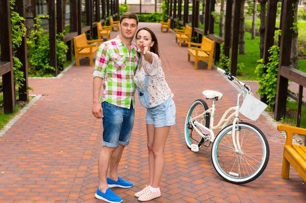 자전거를 탄 젊은 여성이 공원의 아치형 입구에서 남자에게 가는 길을 보여줍니다.