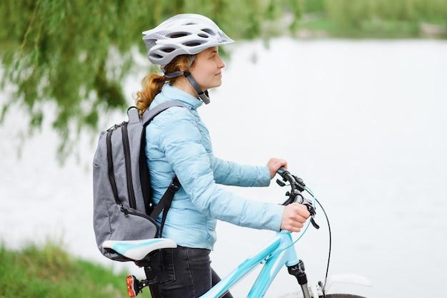 公園を歩いている自転車と若い女性