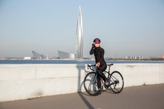 超高層ビルの塔の背景に自転車で休んでいる若い女性