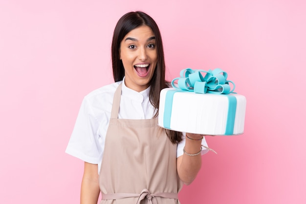 Young woman with a big cake over isolated wall with surprise and shocked facial expression