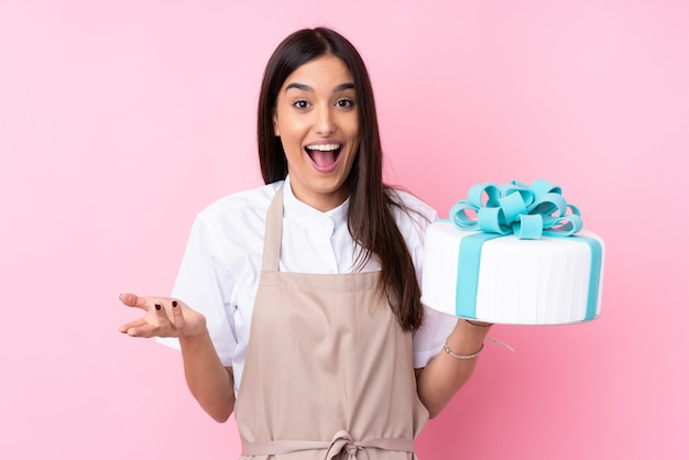 Young woman with a big cake with shocked facial expression