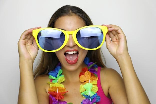 大きな面白いサングラスとカーニバルの花輪を持つ若い女性がカメラに微笑む