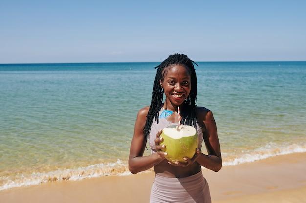 Молодая женщина с большим зеленым кокосом