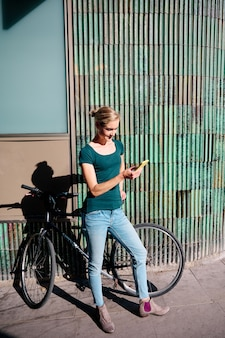 Young woman with bike looking her smartphone