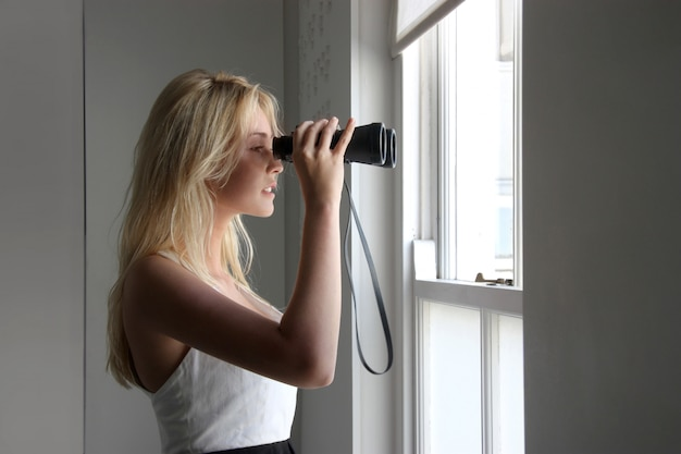 Young woman with a binoculars