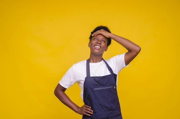 黄色の壁にポーズをとって黒いエプロンを持つ若い女性