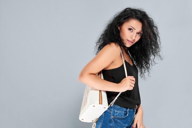 Молодая женщина с черными вьющимися волосами, несущая белый рюкзак с узором и застежкой-молнией.