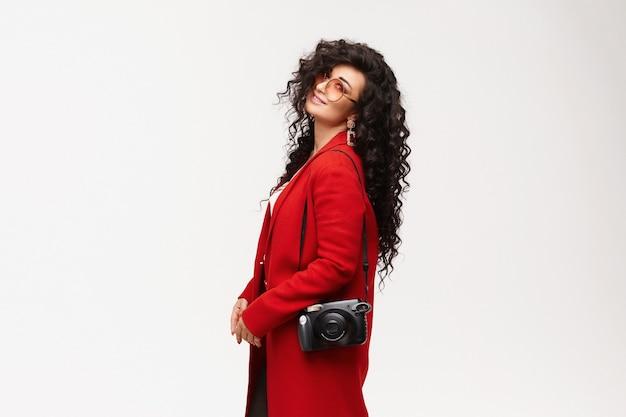 Молодая женщина с черными вьющимися волосами в красном пальто и круглых очках позирует