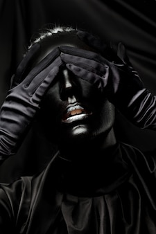 Young woman with black face paint on a black background