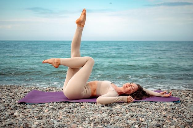 Молодая женщина с инструктором по фитнесу с черными волосами в леггинсах и топах делает растяжку и пилатес