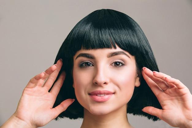 黒い髪のポーズを持つ若い女性。ボブのヘアカットと魅力的なブルネット。両手で触れるモデル。