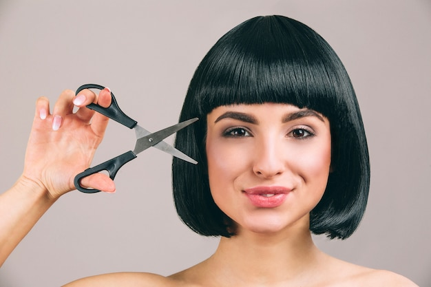 Young woman with black hair posing. cheerful nice confident brunette with bob haircut looking straight. holding opened scissors.