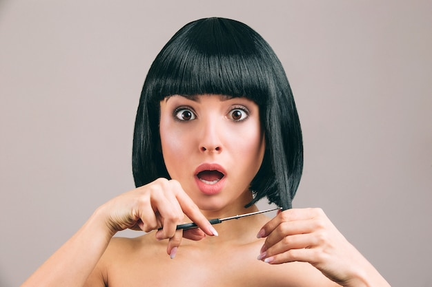 Young woman with black hair posing. cutting pieces of hair from bob haircut. holding scissors in hand. amazed and scared looking.