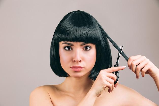 Молодая женщина с черными волосами позирует. серьезная уверенная брюнетка с стрижкой боба. держа ножницы и подстригая кусок волос.
