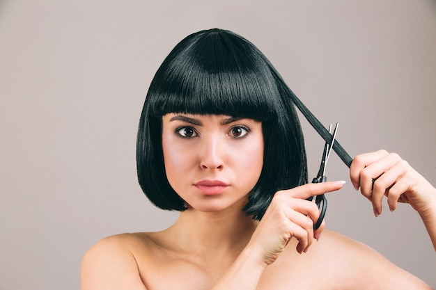 Young woman with black hair posing. serious confident brunette with bob haircut. holding scissors and cutting piece of hair.