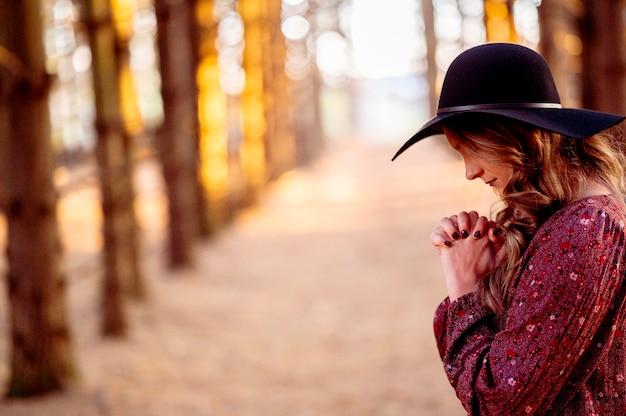 Giovane donna con cappello nero in preghiera