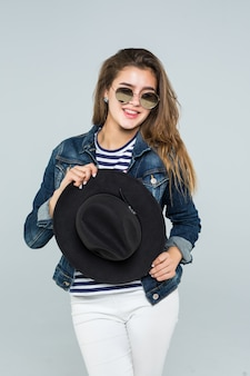 Young woman with black hat and sunglasses isolated on white background