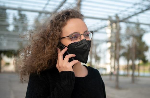 Молодая женщина с черной маской разговаривает по телефону на улице
