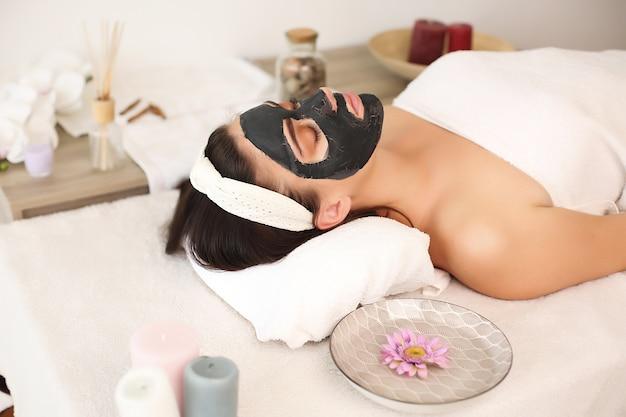 Молодая женщина с черной маской лечения в спа-салоне