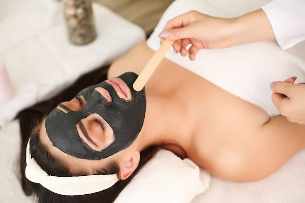 Young woman with black mask treatment at the spa