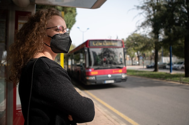 Young woman with black mask waiting for the bus in the city