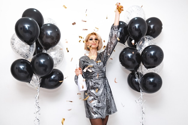 Young woman with black and silver balloons
