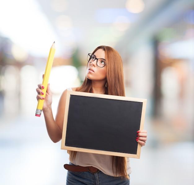 黒板や鉛筆を持つ若い女性