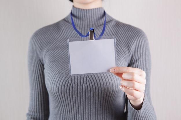 Молодая женщина с пустым значком на белом