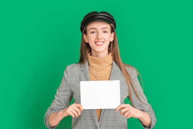 Молодая женщина с пустой картой на цветном фоне