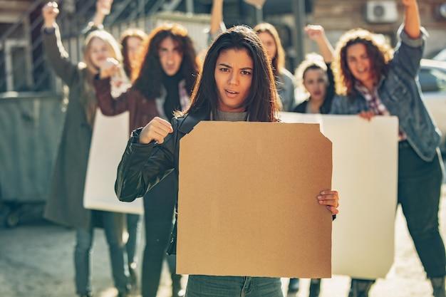 路上で女性の権利と平等について抗議する人々の前に空白のポスターを持つ若い女性。職場の問題、男性のプレッシャー、家庭内暴力、ハラスメントについてのミーティング。コピースペース。