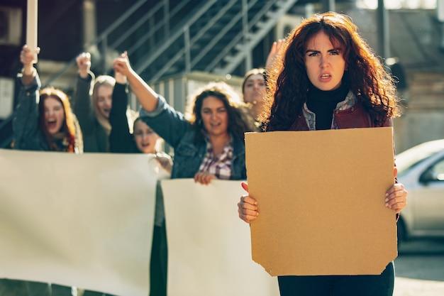 路上で女性の権利と平等について抗議する人々の前に空白のポスターを持つ若い女性。