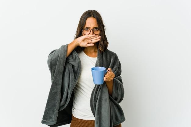 Молодая женщина с одеялом, изолированным на белой стене, делает жест отрицания