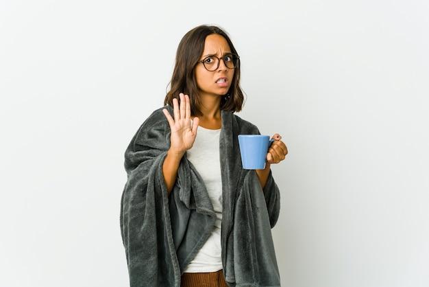Молодая женщина с одеялом изолирована на белой стене, отвергая кого-то, показывающего жест отвращения