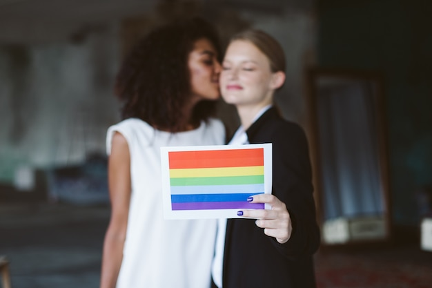 Young woman with blond hair in black suit holding lgbt flag in hand while pretty african american woman with dark curly hair in white dress kissing her in cheek on wedding ceremony