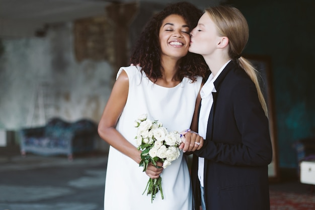 Young woman with blond hair in black suit kissing in cheek pretty african american woman with dark curly hair in white dress with bouquet of flowers in hand on wedding ceremony