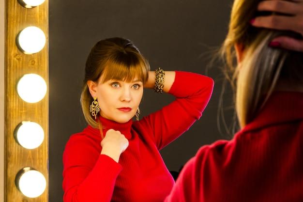 ドレッシングテーブルに赤のブロンドの髪を持つ若い女性は鏡で彼女の髪をまっすぐにします