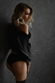 Young woman with blond hair and sexy perfect body, in stockings, lingerie and leather jacket.