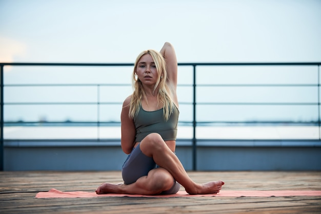 Young woman with blond hair and slim body make yoga exercise on the yoga mat on wooden terrace at sunset.