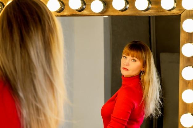 ドレッシングテーブルに赤で金髪の緩い髪の若い女性は鏡で彼女の髪をまっすぐにします