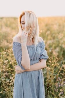 Молодая женщина со светлыми волосами, стоя в поле в синем платье, улыбаясь