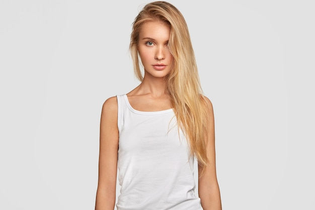 Young woman with blonde long hair combed on one side, wears oversized casual white t shirt