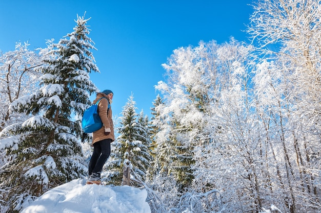 冬の森でハイキングの青いバックパックを持つ若い女性