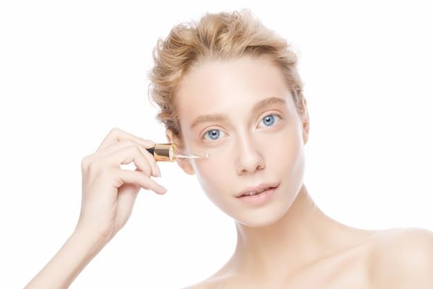 青い目とブロンドの髪を持つ若い女性は、白で隔離の彼女の顔に血清を適用します