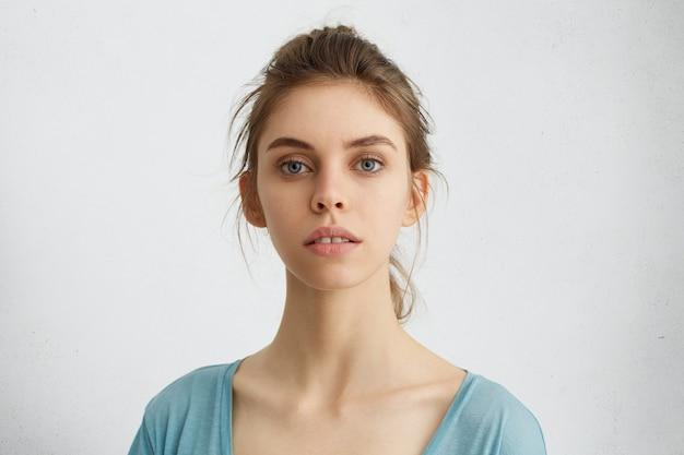 Giovane donna con gli occhi azzurri e capelli appuntati che guarda orgogliosamente orgogliosa di avere successo durante le lezioni. femmina caucasica con bel viso che mostra la sua eleganza