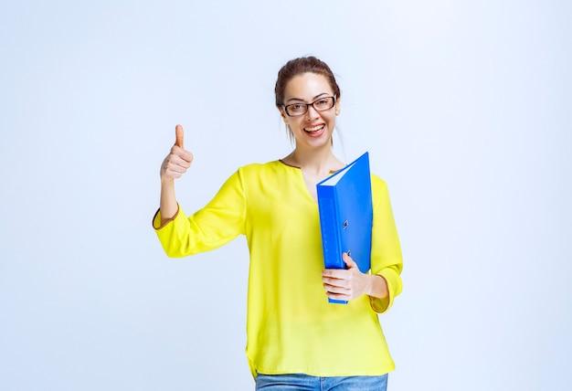 Giovane donna con una cartella blu che mostra il segno di divertimento