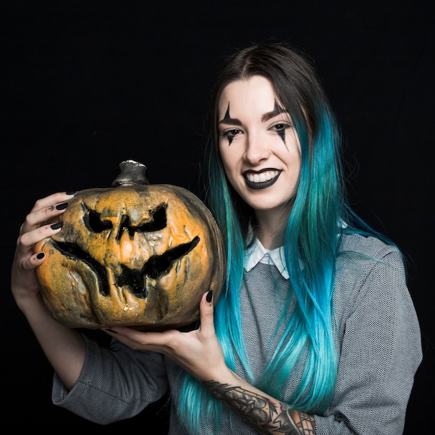 Young woman with blue hair holding pumpkin