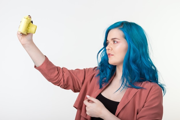 Молодая женщина с синими волосами держит ретро фотоаппарат на белой стене